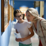 A photo showing a young girl and a woman looking at a painting during a museum visit.