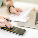 Close-up of a woman using a calculator at her desk