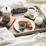 A photo showing a luxurious breakfast in bed with coffee and a croissant.