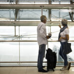 Image of a mature couple in an airport. Tax economics show that we should be defending big business and the many capabilities it provides, including air travel.