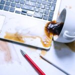 An image of an overturned coffee cup with coffee spilled on an expensive laptop.