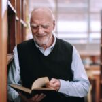 A photograph of a senior man smiling and reading a book in a library.