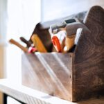 A photo showing a wooden toolbox with a variety of tools.