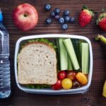 A photo showing a healthy packed lunch with water, sandwich, fruits and veggies.