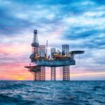 A photo showing an offshore oil rig in the middle of the ocean.
