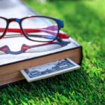 A photo showing an investing book in the grass with glasses.