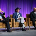 A photo showing John Mackey, Mark Skousen and Kevin O'Leary during their debate at the 2019 FreedomFest.