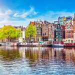 A photo showing row houses along a canal in Amsterdam, Netherlands.