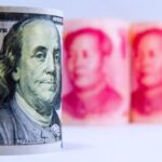 A photo showing U.S. $100 banknotes in the foreground and Chinese yuan banknotes in the background.