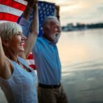 A photo showing a happy, mature couple celebrating with an American flag on the waterfront.