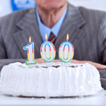 A photo showing a man in a suit behind a 100th birthday cake, waiting to blow out the candles.