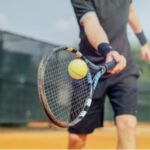 A photo showing a man swinging a tennis racket.