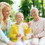 A photo showing a mother and grandmother with a young granddaughter blowing bubbles and enjoying time outside.