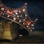 A photo showing a bejeweled crown resting atop a book.
