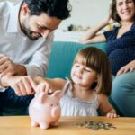 A photo showing two parents with a young daughter saving money in her piggy bank.