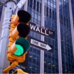 A photo showing a traffic signal with a green light at a Wall Street intersection.