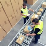 An overhead photo showing two warehouse employees working on order fulfillment.