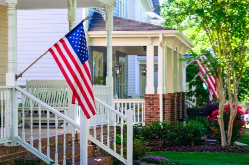 A photo showing a row of homes displaying American flags.