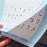 A photo showing a person's hand flipping through the pages of a calendar.