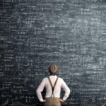 A photo showing a man standing in front of a blackboard contemplating a complex equation.