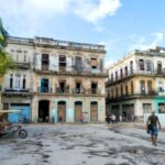 A photo showing people walking around dilapidated buildings in a poor area of Havana, Cuba.
