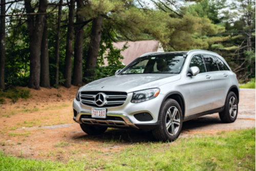 A photo showing a new Mercedes SUV parked in a dirt driveway.
