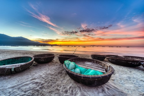 A photo of a sunrise over fishing boats on a beach in Danang City, Vietnam.