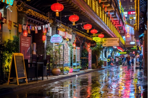 A photo showing businesses lining a street on a rainy night in Chongqing, China.