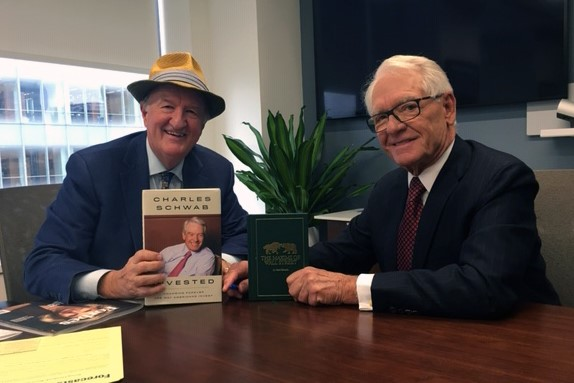A photo of Mark Skousen and Charles Schwab exchanging their books.