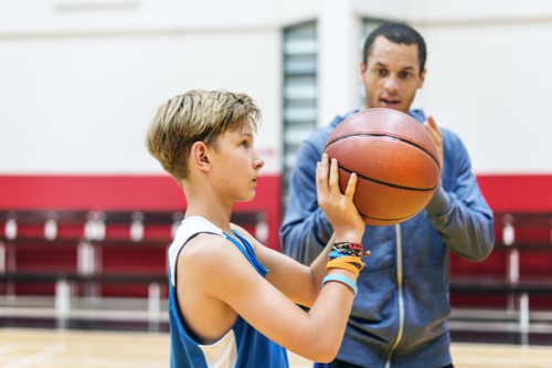 A photo showing a young boy being coached as he practices basketball.