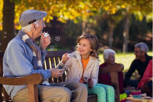 A photo of a grandfather sitting on a park bench with his granddaughter blowing bubbles.