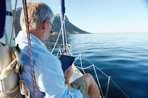 A photo showing a mature man sitting on a sailboat using a tablet computer.