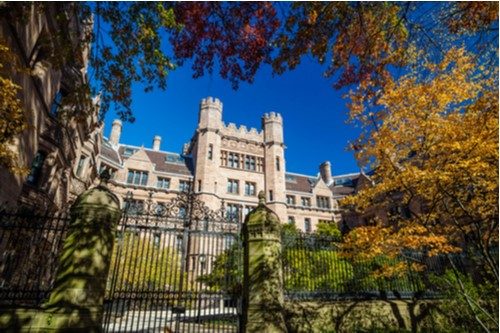 A photo showing a historical building on the Yale University campus during the fall season.