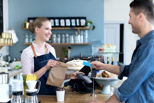 A photo of a barista and customer both smiling as the customer pays for his order.