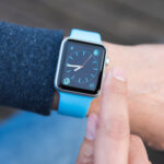A photo of a person checking the blue Apple Watch on their wrist.
