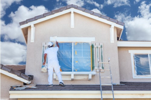 A photo showing a male house painter working on the exterior of a house.