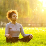 A woman meditates in the grass