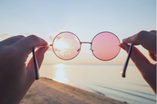 Two hands holding rose-colored-glasses in front of a beautiful beach sunset.