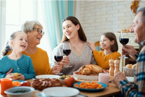 A grandmother, mother and daughters sharing smiles and cheers over Thanksgiving dinner.