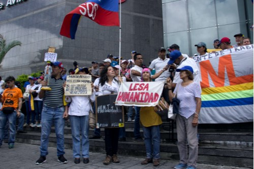 A photo of individuals carrying signs and flags in protest of Venezuelan president Nicolás Maduro.