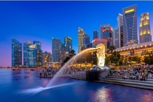 A nighttime view of Marina Bay in Singapore with the skyline in the background.