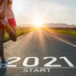 """A runner stretches on an open road at a starting line marked """"2021 start."""""""