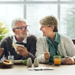 A photo of a smiling senior couple enjoying lunch together.