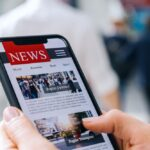 A photo showing a person viewing a news website on their smartphone.