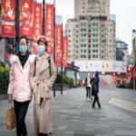 Two people walking while wearing face masks