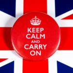 "A photo showing a button reading ""Keep Calm and Carry On"" displayed on top of the United Kingdom Union Jack flag."