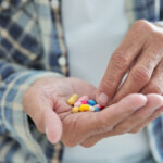 A photo showing a senior man's hands holding many pills