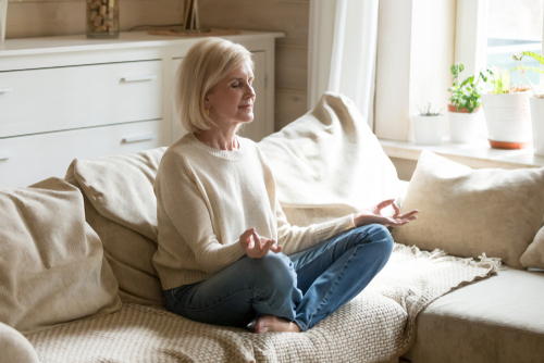 A photo of a mature woman sitting on her couch meditating.