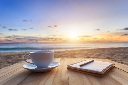 A photo showing a cup of coffee and a notebook resting atop a wooden table on the beach at sunrise.