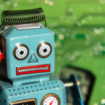 A photo of a vintage toy robot in front of a computer circuit board background.